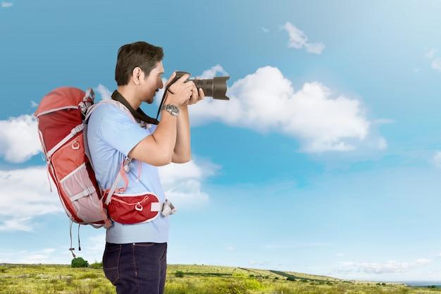 Vista lateral del fotógrafo asiático con mochila Foto Premium