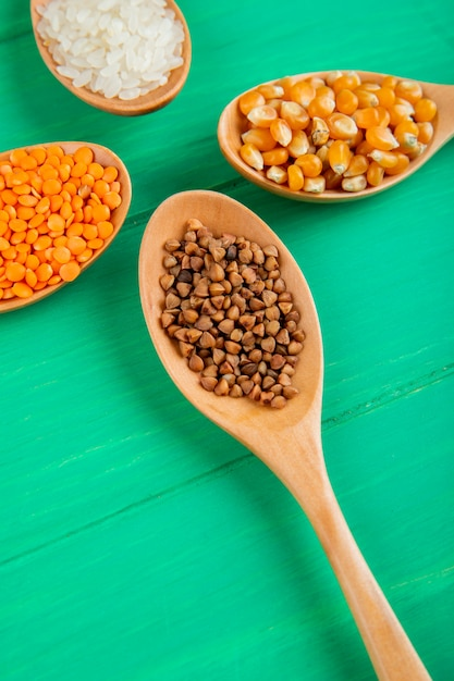 Vista lateral de granos de cereales y montones de semillas en cucharas de madera callos arroz trigo sarraceno y lentejas rojas Foto gratis