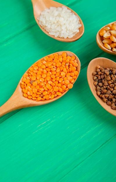 Vista lateral de granos de cereales y semillas en cucharas de madera callos arroz trigo sarraceno y lentejas rojas en mesa verde Foto gratis