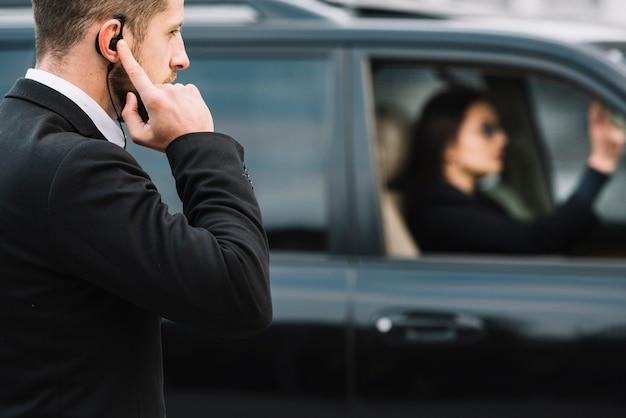 Vista lateral del guardia de seguridad que vigila al cliente Foto gratis