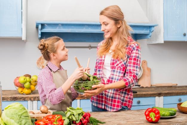 Vista lateral de una hija ayudando a su madre para preparar ensalada Foto gratis