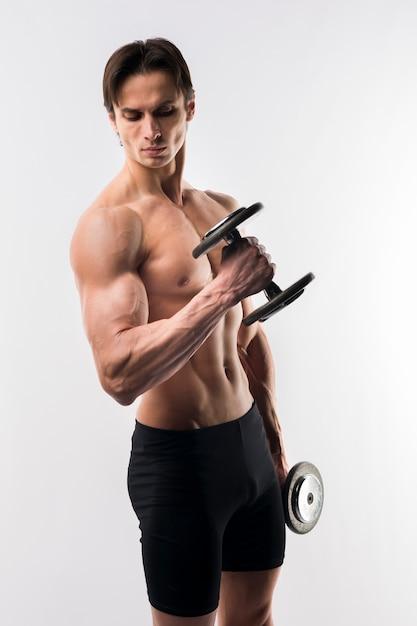 Vista lateral del hombre atlético sin camisa con pesas Foto gratis