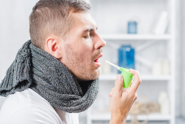 Vista lateral de un hombre chorros de garganta con spray. Foto gratis