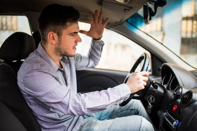 Vista lateral del hombre enojado en ropa casual conduciendo coche Foto gratis