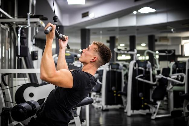 Vista lateral del hombre en el gimnasio levantando pesas Foto gratis