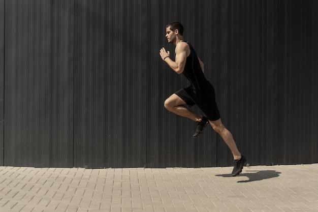 Vista lateral de un hombre joven y atlético en forma saltando y corriendo. Foto gratis