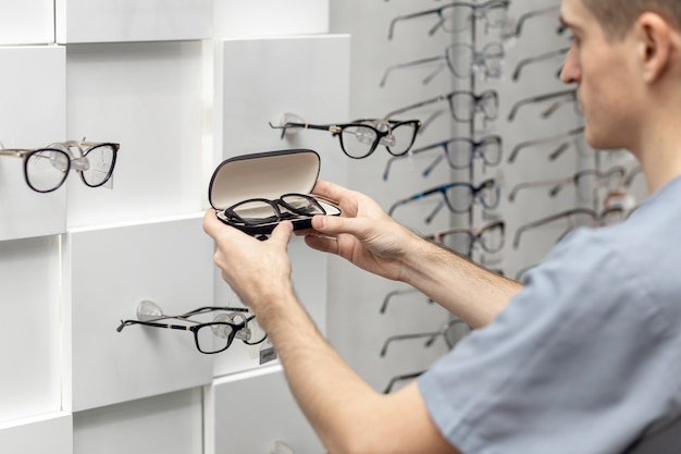 Vista lateral del hombre mirando un par de anteojos en las manos Foto gratis