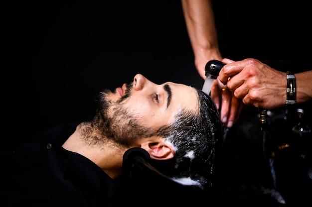 Vista lateral del hombre que tiene su cabello lavado en el salón Foto gratis