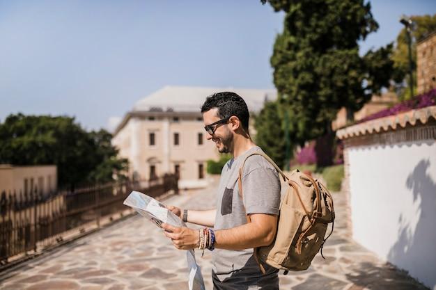 Vista lateral del hombre sonriente mirando el mapa de pie en la calle Foto gratis