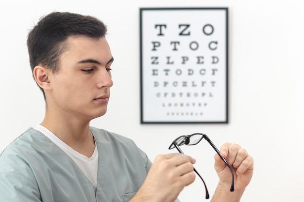 Vista lateral del hombre sosteniendo y mirando un par de anteojos Foto gratis