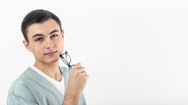 Vista lateral del hombre sosteniendo sus gafas en la mano con espacio de copia Foto gratis