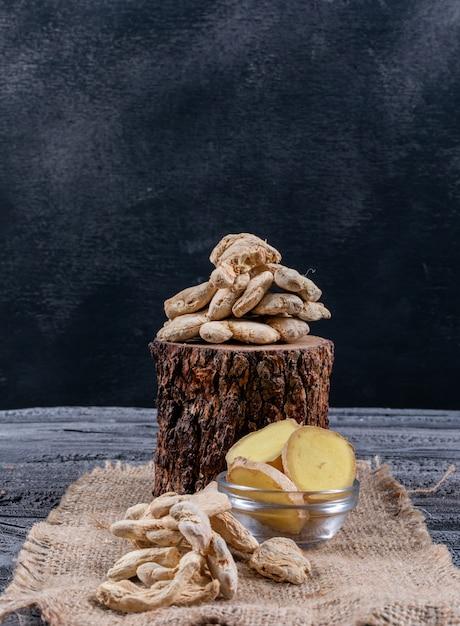 Vista lateral de jengibre con rodajas de jengibre en trozo de madera, tela de saco y fondo de madera oscura. vertical Foto gratis