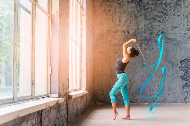 Vista lateral de una joven bailando con cinta azul Foto gratis