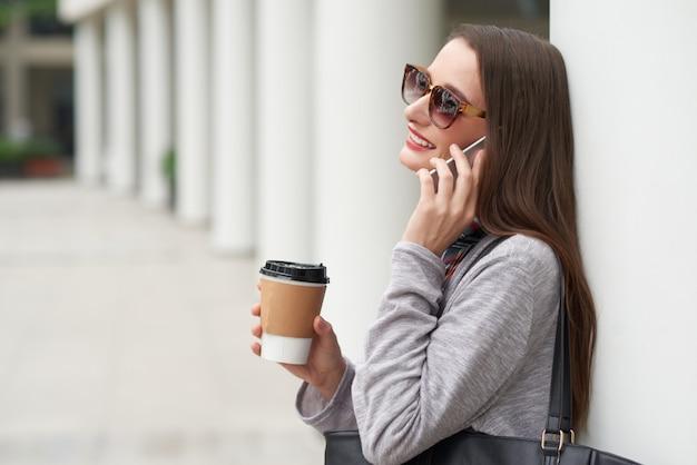 Vista lateral de la joven en gafas de sol haciendo llamada telefónica apoyándose en la pared del edificio Foto gratis