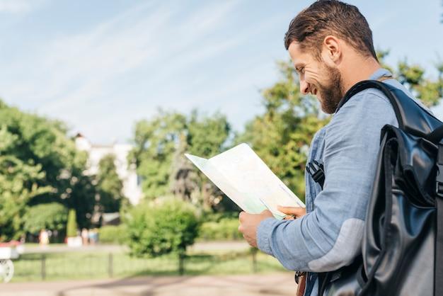 Vista lateral del joven sonriente llevando mochila y leyendo el mapa al aire libre Foto gratis