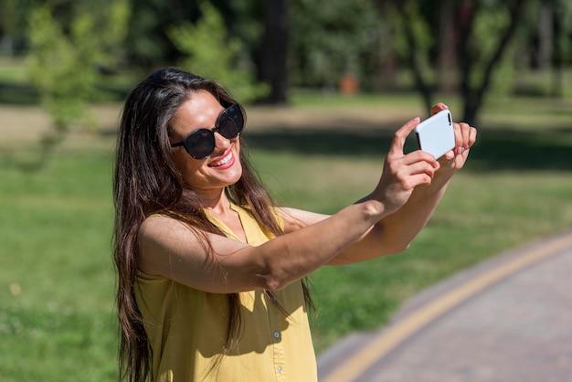 Vista lateral de la madre tomando fotografías de su familia con el smartphone mientras está al aire libre Foto gratis