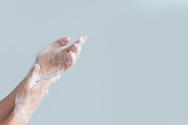 Vista lateral de manos cubiertas de espuma de jabón Foto gratis