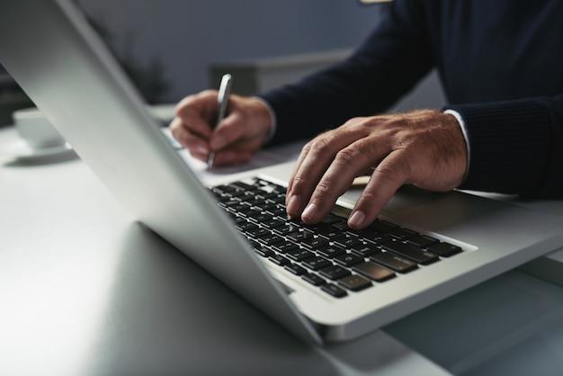 Vista lateral de manos masculinas escribiendo en el teclado del portátil Foto gratis