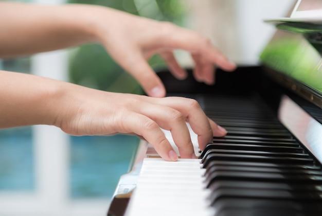 Vista lateral de las manos de una mujer tocando el piano Foto gratis