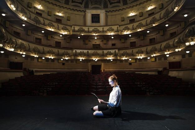 Vista lateral de un manuscrito de lectura mime femenino en el auditorio vacío Foto gratis