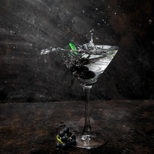 Vista lateral martini en un vaso con aceitunas Foto gratis