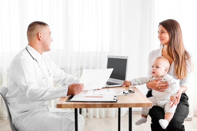 Vista lateral médico hablando con la madre de un bebé Foto gratis