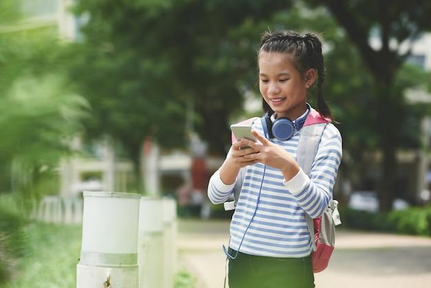 Vista lateral del mensaje de texto de una niña asiática a sus padres después de la escuela de pie al aire libre en un agradable día de primavera Foto gratis