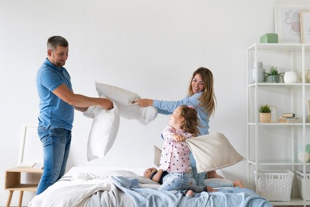 Vista lateral de miembros de la familia peleando con almohadas Foto gratis