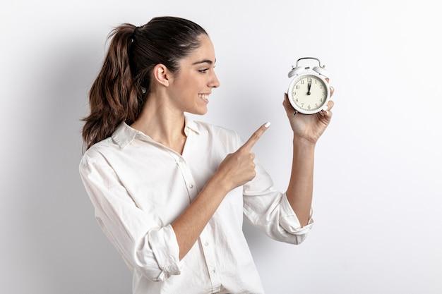 Vista lateral de la mujer apuntando al reloj de mano Foto gratis