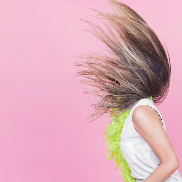 Vista lateral de la mujer arrojando su cabello largo sobre fondo rosa Foto gratis