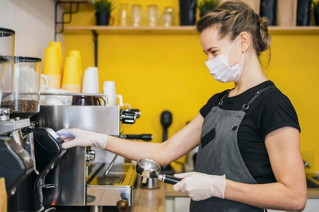 Vista lateral de la mujer barista con guantes de látex preparando café para máquina Foto gratis