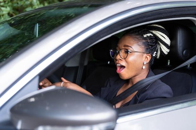 Vista lateral de la mujer emocionada por conducir su coche personal Foto gratis