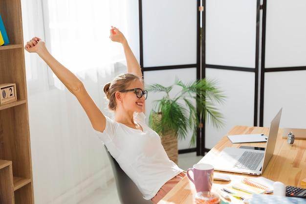 Vista lateral de la mujer feliz que trabaja en casa Foto gratis