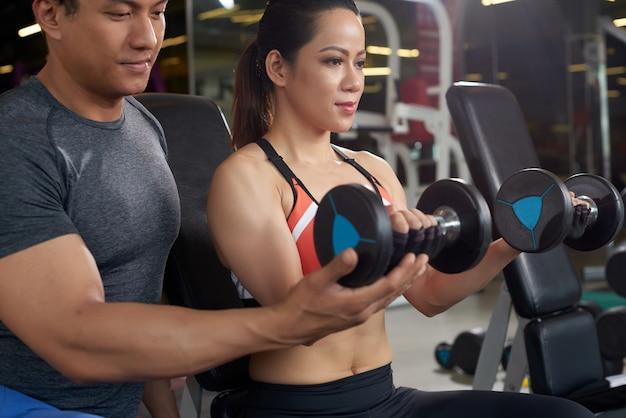 Vista lateral de la mujer en forma trabajando con el entrenador personal de levantamiento de pesas Foto gratis