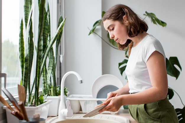 Vista lateral, mujer joven, lavar platos Foto gratis