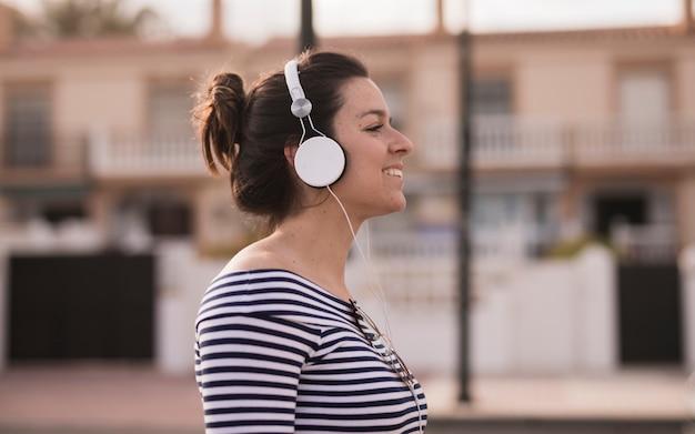 Vista lateral de una mujer joven que disfruta de la música que escucha en el auricular Foto gratis