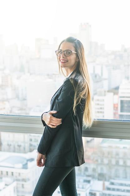 Vista lateral de la mujer joven sonriente que se coloca cerca de la ventana Foto gratis