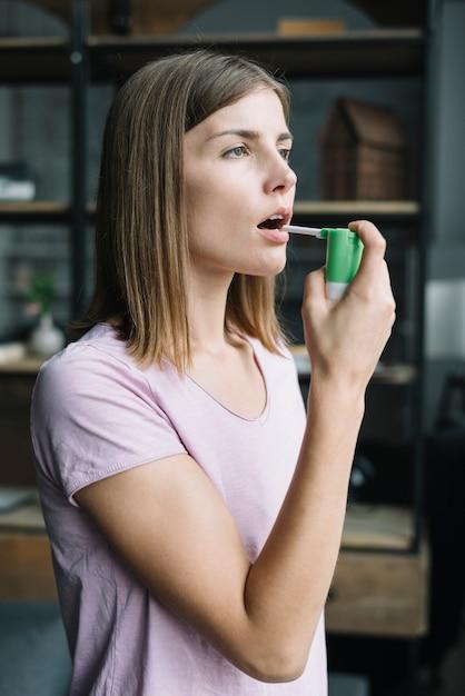 Vista lateral de una mujer joven usando spray para la garganta Foto gratis