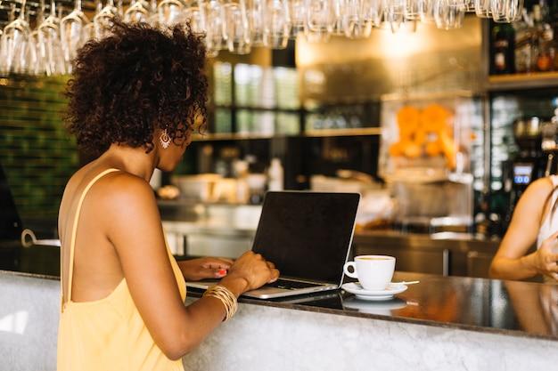 Vista lateral, de, mujer joven, usar la computadora portátil, en, barra, mostrador Foto gratis