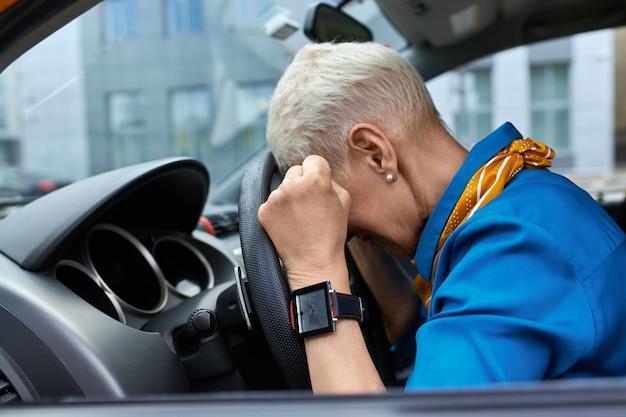 Vista lateral de una mujer de mediana edad estresada infeliz apretando los puños y apoyando la cabeza en el volante, atascada en un atasco, llegar tarde al trabajo o tener un accidente automovilístico, sentado en el asiento del conductor Foto gratis