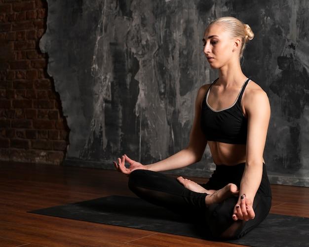 Vista lateral mujer meditando con fondo de estuco Foto gratis