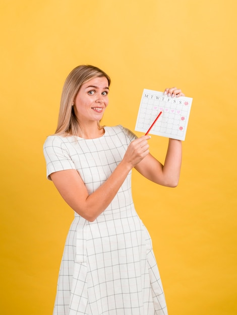 Vista lateral mujer mostrando su calendario de período Foto gratis