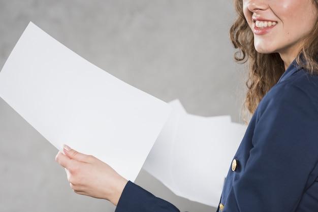 Vista lateral de la mujer con papeles Foto Premium