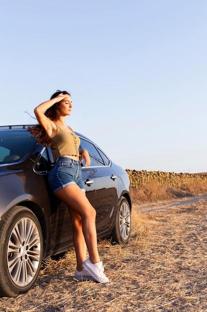 Vista lateral de la mujer posando mientras mira el sol y descansando en el coche Foto gratis