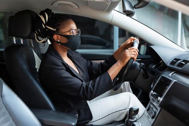 Vista lateral de la mujer que conducía su coche mientras llevaba una mascarilla Foto gratis