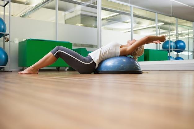 Vista lateral de la mujer que la estira de nuevo en el gimnasio