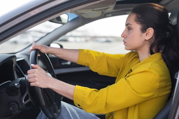 Vista lateral mujer segura conduciendo su coche Foto gratis