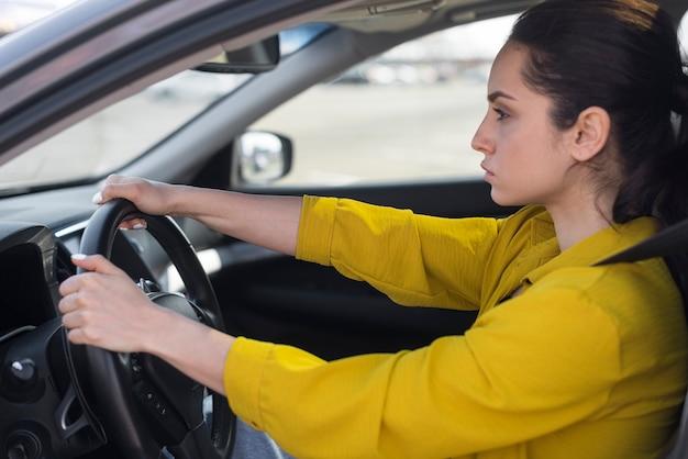Vista lateral mujer segura conduciendo Foto gratis