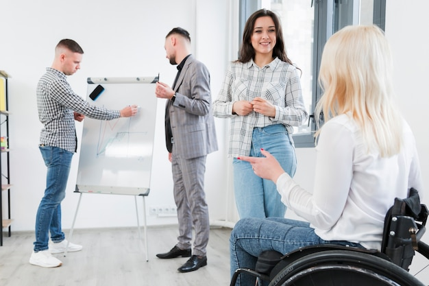 Vista lateral de la mujer en silla de ruedas conversando con un compañero de trabajo en la oficina Foto gratis
