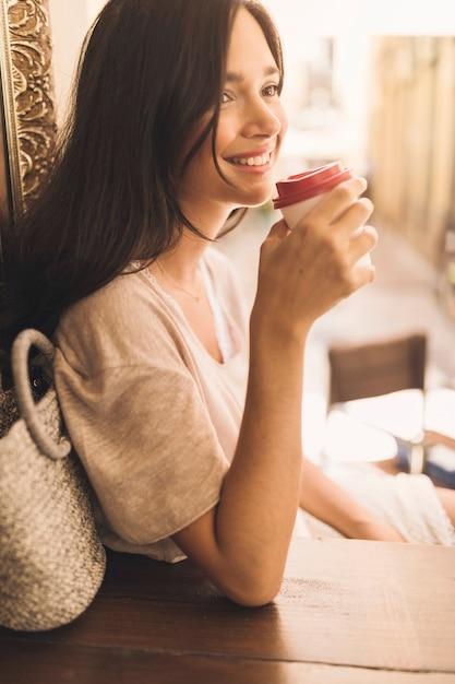Vista lateral de la mujer sonriente bebiendo café desechable Foto gratis